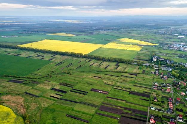春または夏の日の田園風景。日当たりの良い夜明けの緑、耕した、咲くフィールド、家の屋根の空撮。ドローン写真。