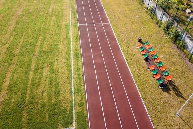Взгляд сверху красных идущих следов и лужайки зеленой травы. инфраструктура для занятий спортом.