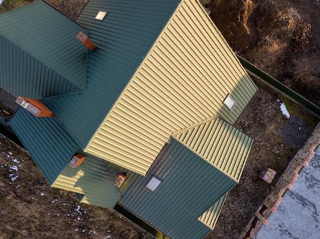 晴れた日にフェンスで囲まれた庭に鉄片屋根の新しい住宅コテージの空撮。