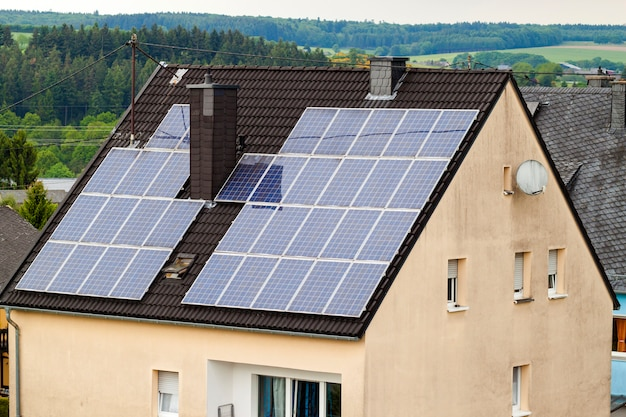 郊外の家の屋根にある再生可能なクリーンなグリーン省エネの効率的なソーラーパネル。