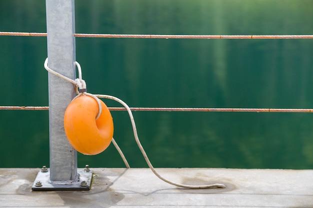 Желтый пластичный буй прикрепленный к металлическому ограждению на берегу озера с зеленой водой.