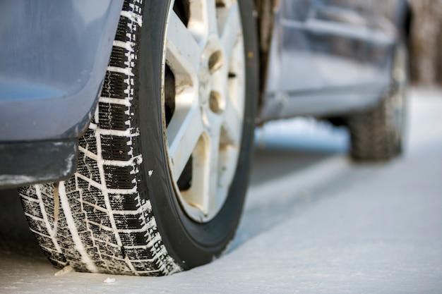 冬の日に雪道に駐車した車のタイヤのクローズアップ。輸送および安全コンセプト。