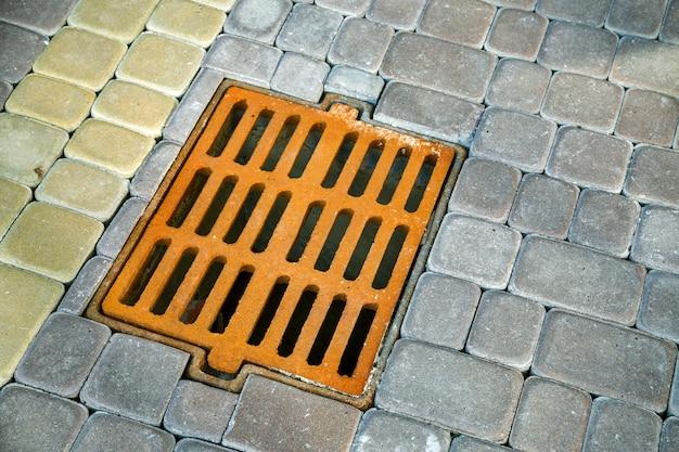 Старый ржавый металлический желоб для дождевой воды на тротуаре вымощенный камнем.
