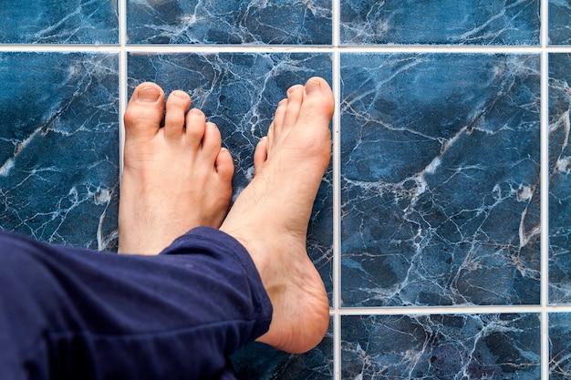 Молодой человек, пересекая ноги на квадратные плитки. вены в ногах видны.