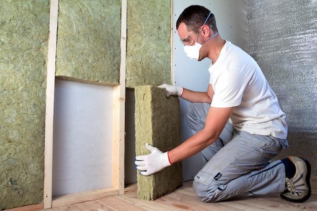 防寒用の将来の家の壁のために木枠のロックウール断熱材を保護する保護ゴーグルと人工呼吸器の労働者。快適で暖かい家、経済、建設、改修のコンセプト