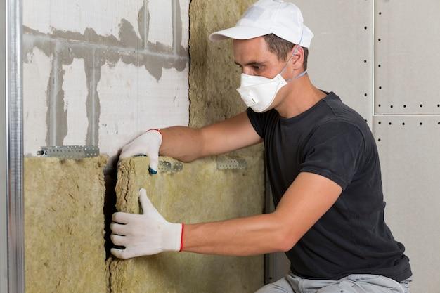 防寒マスクの将来の家の壁の木製フレームのロックウール断熱材を保護する保護マスクの労働者。快適で暖かい家、経済、建設、改修のコンセプト