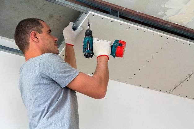 建設作業員は、乾式壁で吊り天井を組み立て、ドライバーで乾式壁を天井の金属フレームに固定します。
