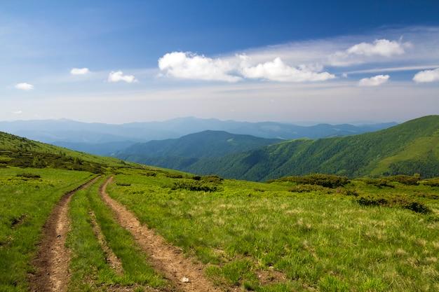 明るい青空コピースペース背景に木質の山の尾根につながる緑の草が茂った丘の上の汚れ車トラック。観光と旅行のコンセプト。