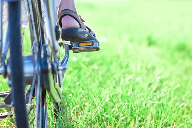 Женская нога на велосипедной педали на зеленой траве крупным планом