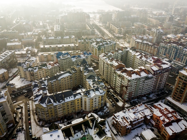 Воздушное черно-белое зимнее вид сверху современного центра города с высокими зданиями и припаркованными автомобилями на снежных улицах.