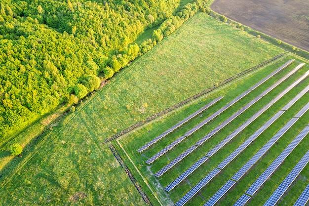 Большое поле солнечной фотоэлектрической системы, производящей возобновляемую чистую энергию на зеленой траве