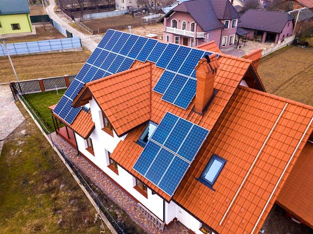 屋根の上の青い光沢のある太陽光発電システムと新しいモダンな住宅コテージの空中のトップビュー。再生可能な生態学的なグリーンエネルギー生産の概念。