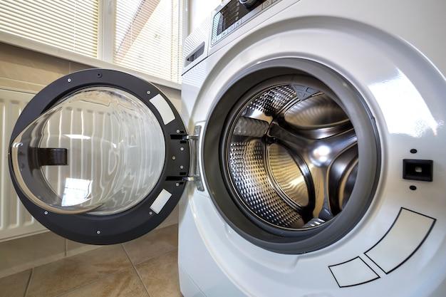 開いたドアのインテリアとモダンな洗濯機のインテリアのクローズアップの詳細。銀色の光沢のあるステンレスドラム、デザインと技術。
