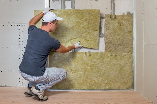ミネラルロックウール断熱材で部屋の壁を断熱する労働者。