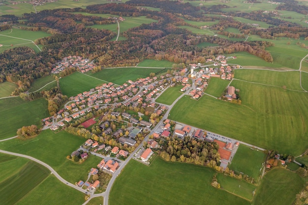 Аэрофотоснимок маленького города с красными черепичными крышами среди зеленых полей фермы и далекого леса в летнее время.
