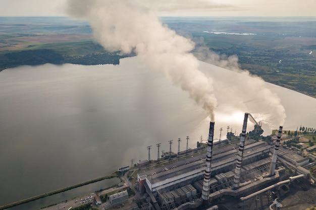 石炭発電所からの灰色の煙と高い煙突パイプの空撮。化石燃料による電気の生産。