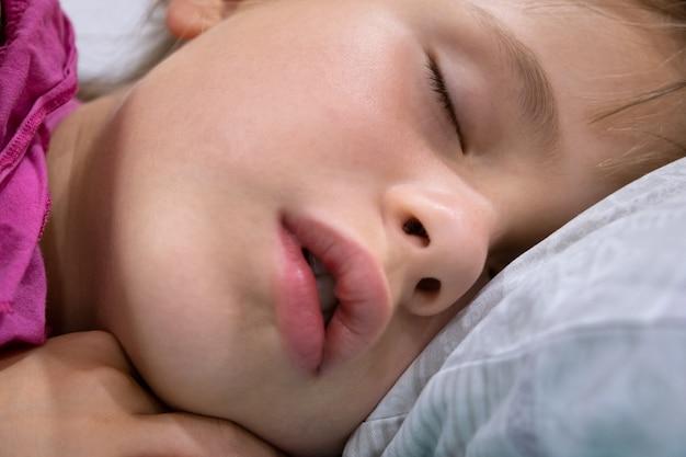 少し口を開けて、自宅のベッドで寝ている髪の周りに散らばっているかわいい子供の女の子の顔のクローズアップ。