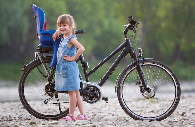 現代の自転車の前に小石の上に立って青いドレスの小さなブロンドの女の子