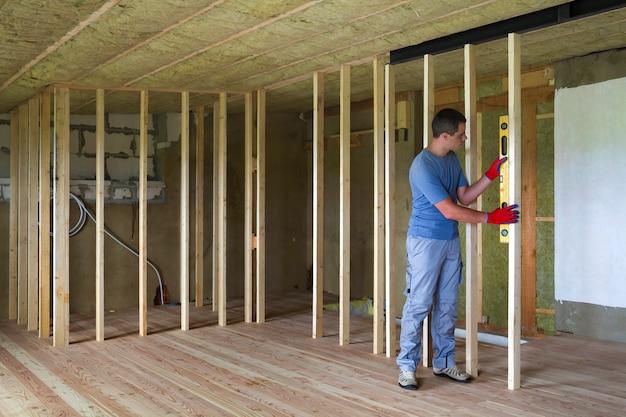 再建の下で断熱天井と空の未完成の屋根裏部屋で作業する人