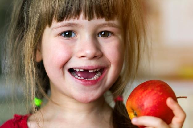 歯のない少女は笑顔し、赤いリンゴを保持