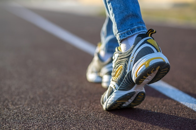 Закройте вверх ног женщины в тапках спорта и голубых джинсах на идущей майне на внешней спортивной площадке.