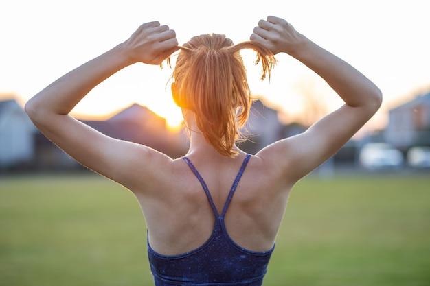 トレーニング前に日の出を楽しんでいる調達の腕と屋外で立っている赤い髪の容陽気な女性のクローズアップ。