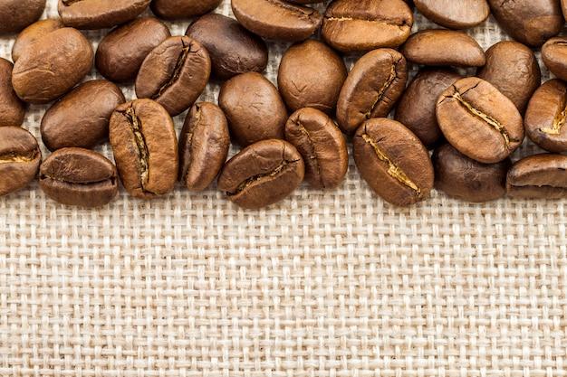 黄麻布の荒布キャンバスとコーヒー豆の写真の背景。コピースペース。コーヒーボーダー