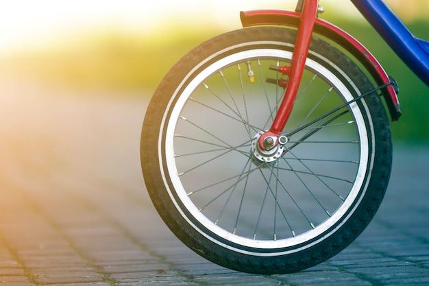 灰色の舗装のティーンエイジャー自転車前輪のクローズアップの詳細