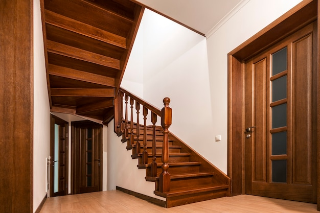 Современные коричневые дубовые деревянные лестницы и двери в новом отремонтированном интерьере дома