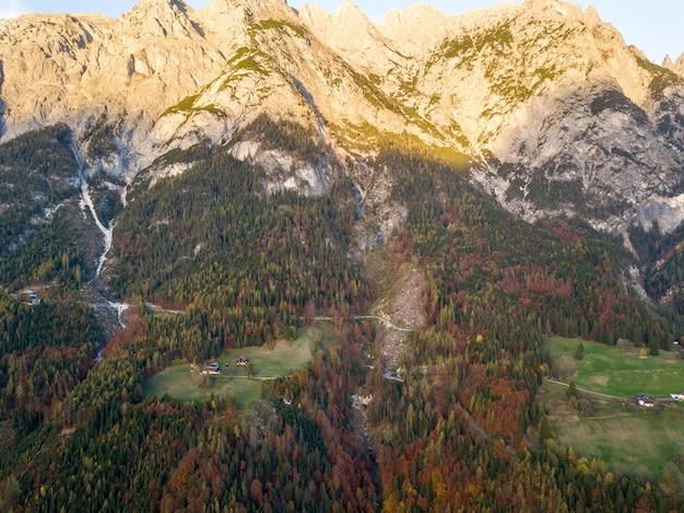 Вид с воздуха величественных европейских гор альп покрыты вечнозеленым сосновым лесом осенью.
