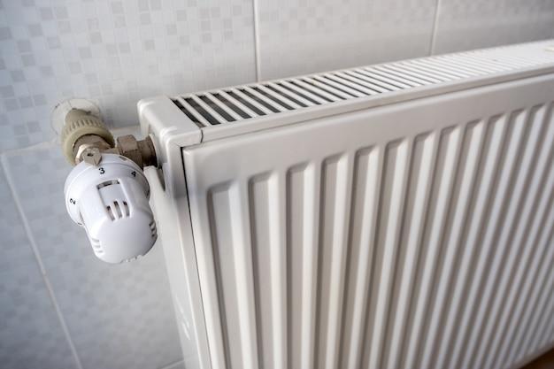 内側の壁にある金属製ラジエーターの快適な温度調節のためのラジエーターバルブの加熱のクローズアップ。