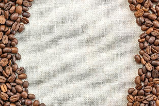 黄麻布の荒布キャンバスとコーヒー豆を丸い写真の背景に配置します。コピースペース。コーヒーボーダー