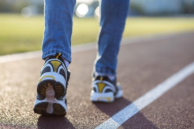 スポーツスニーカーで女性の足のクローズアップと屋外スポーツコートで実行中のレーンにブルージーンズ。