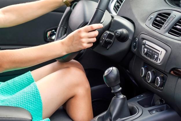 Красивые загорелые стройная женщина водитель ноги в машине. девушка в платье за рулем автомобиля