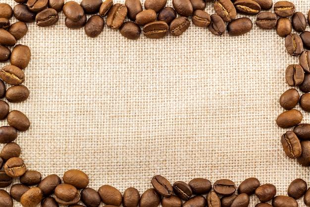 黄麻布の荒布キャンバスとコーヒー豆は、円形の写真の背景に丸い配置。コピースペース。コーヒーボーダー