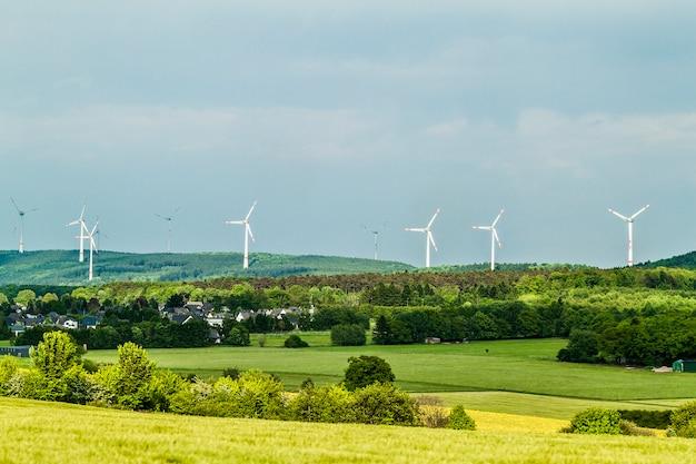 風力タービン再生可能エネルギー源の夏の風景、澄んだ青い空と手前の村または町