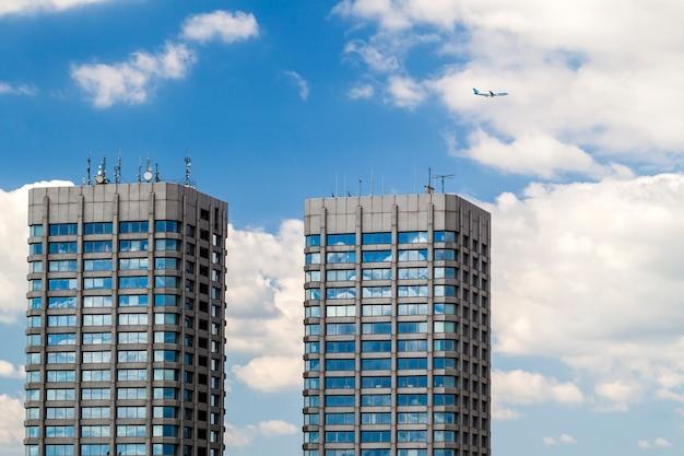 モダンなガラスとコンクリートの高層ビルと空の飛行機