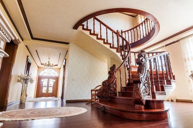 Современная архитектура интерьера с классической элегантной роскошной прихожей с изогнутыми глянцевыми деревянными ступеньками лестницы в современном доме