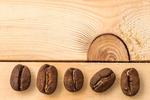 黄色のテクスチャ木製ボードの背景に茶色のコーヒー豆をクローズアップ。