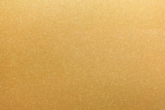 金色のキラキラオレンジ黄色の表面に白い不規則な斑点が点滅、コピースペースの背景。