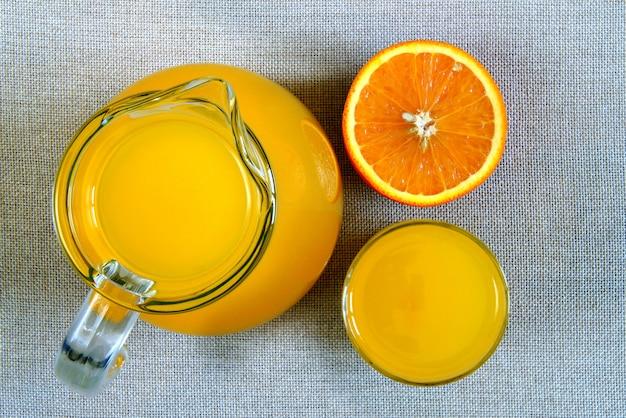 Кувшин и стакан апельсинового сока и спелых апельсинов сверху, вид сверху на поверхность мешковины мешковины