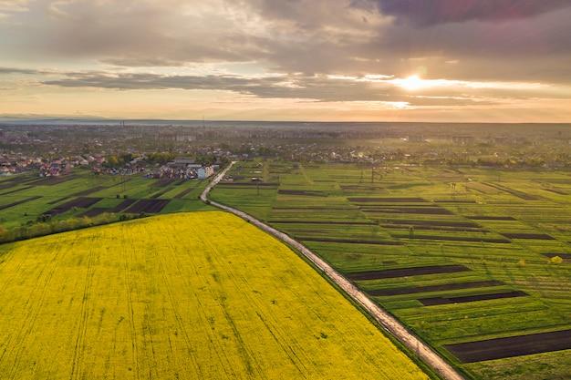 春または夏の日の田園風景。緑、耕した、咲く畑、家の屋根、道路の空撮。