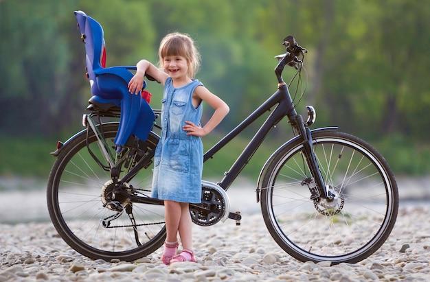 夏の日にぼやけた緑の木々の表面にチャイルドシートと現代の自転車の前の小石の上に立って青いドレスの小さなかなりブロンドの女の子。アクティブなライフスタイルと家族のレクリエーションの概念。