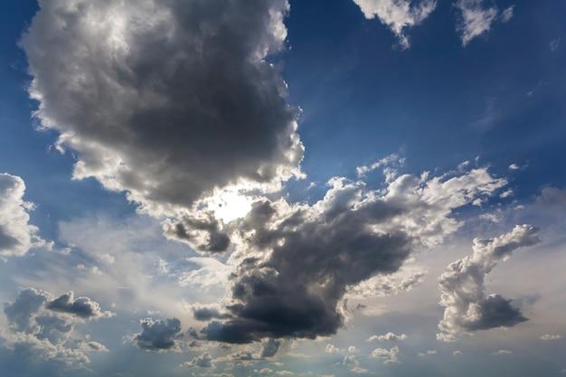 風とともに移動する深い青色の夏空に広がる太陽に照らされた明るい白いふくらんでいる雲の素晴らしいパノラマビュー。自然の美と力、気象学、気候変動の概念。