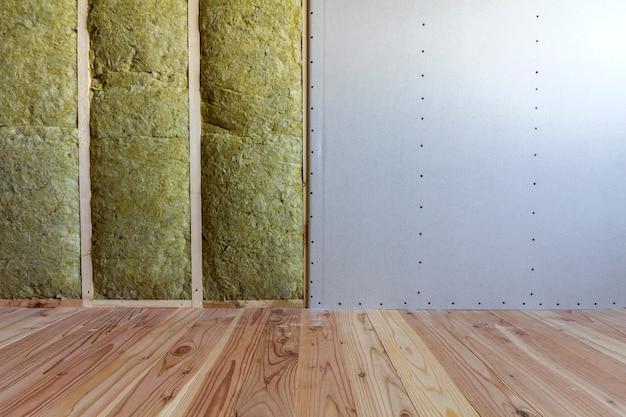 ロックウールで断熱された乾式壁プレートと防寒壁用のグラスファイバー断熱スタッフを備えた将来の壁用の木製フレーム。快適で暖かい家、経済、建設、改修のコンセプト。