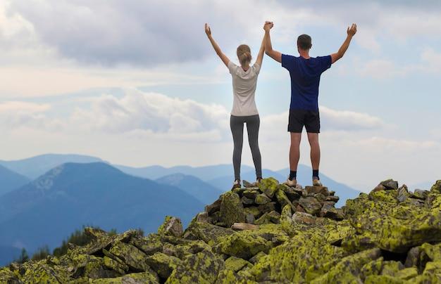 若いカップル、アスレチックボーイ、息をのむような夏の山の景色を楽しみながら岩山の頂上に腕を上げて立っているスリムな女の子の背面図。観光、成功、健康的なライフスタイルのコンセプト。