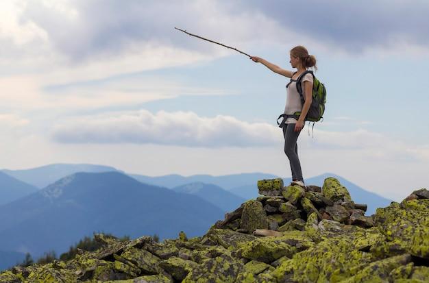 Девушка детенышей тонкая белокурая туристская с рюкзаком указывает с ручкой на туманной панораме горной цепи стоя на скалистой верхней части на яркой голубой сцене неба утра. концепция туризма, путешествий и скалолазания.