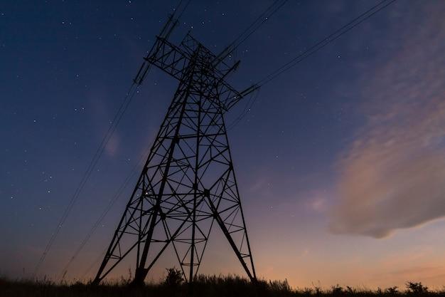 電気の概念の伝送と長距離分布。暗い青い星空のシーンに伸びる電力線と高電圧塔の斜めビュー。