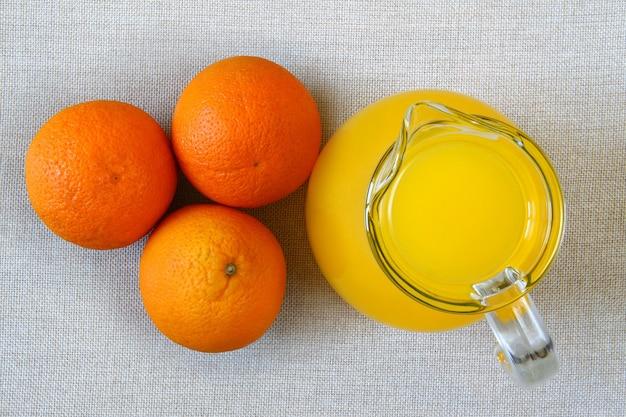 Кувшин и стакан апельсинового сока и спелых апельсинов сверху, вид сверху на сцену из мешковины