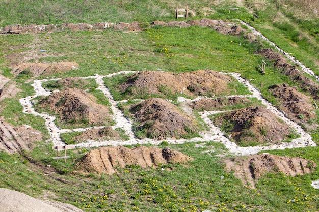 Строительная площадка в зеленом поле. траншеи, вырытые в земле и заполненные цементом в качестве фундамента для будущего дома и забора, груды гравия и песка. концепция строительства, строительства и недвижимости.